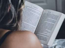 person-reading-book-on-bed