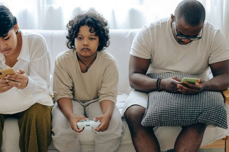 family-spending-time-together-on-couch-with-gadgets